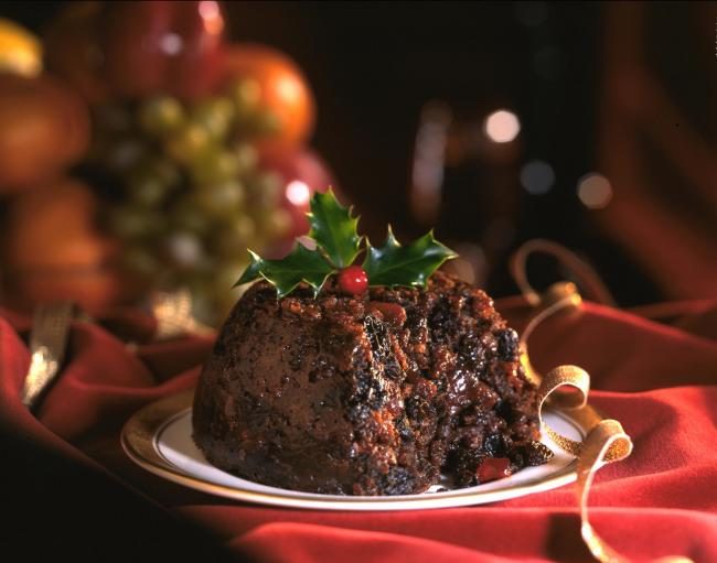 Christmas Pudding decorated with holly leaves  on red background.