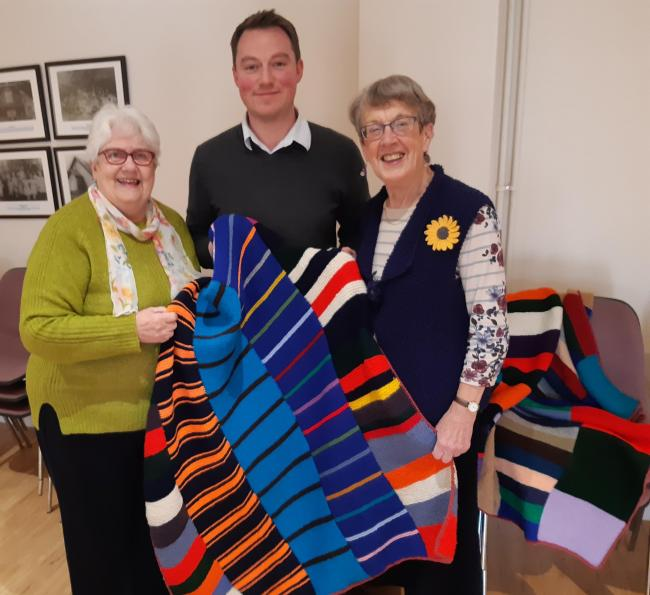 Caption:  Sonia Gwilliam (left) and Anne Coe offer hand-knitted blankets to James Cooper, Operations Manager of The Furniture Scheme in Ludlow.