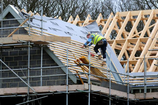 A roofer works on a new house building project