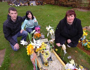 GRIEF: Tom Davies with his partner Jemma Powell and Jemma's mother Tina at the grave of  Phoebe. Picture by John Anyon. 13460601