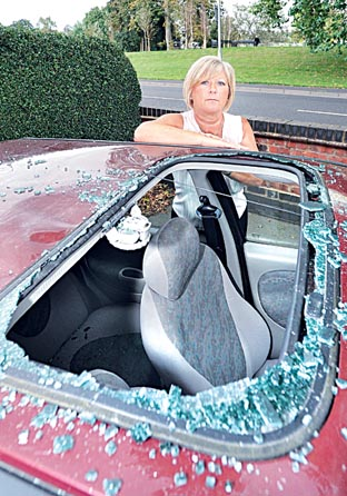 FURIOUS: Bev Churchill next to the smashed sunroof of her Ford Fiesta after a student jumped on the top. Picture: Nick Toogood. 38091702