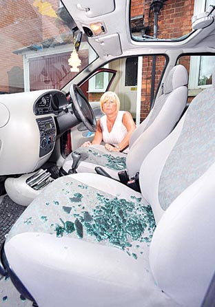 DAMAGE: Bev Churchill with the smashed sunroof on her Ford Fiesta.