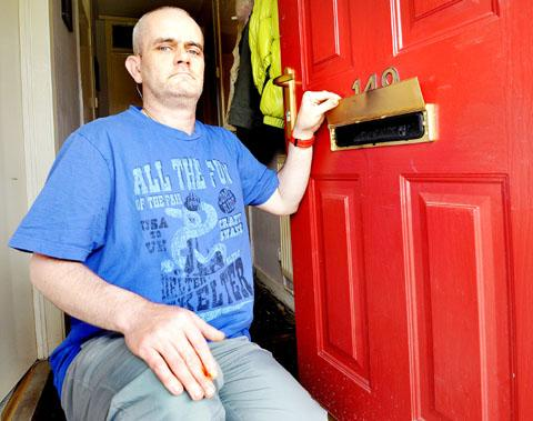 scorched: Anthony Simpson by his front door in Warndon, Worcester, after lighted paper was shoved though the letterbox of the home he shares with his partner. Picture: John Anyon. 26075501