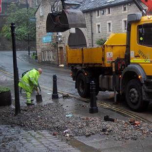 Workers clear rubble that has been washed down from the hills by flash floods in Hebden Bridge, West Yorkshire