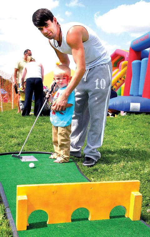 WE LOVE SPORTS: Philip Walker helps his nephew, 23-month-old Tyler Pace-Cox, with mini-golf (30097703)