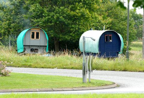 PITCHED: Two of the Romany gipsy wagons set up at the the Norton roundabout on the A4440, near Worcester.