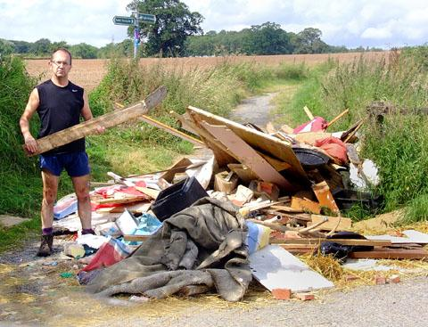 DUMPED: Andrew Brown with fly-tipped rubbish he found on a track off Oldbury Road