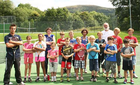 SERVICE: Youngsters enjoy a summer tennis session during a break between rain showers