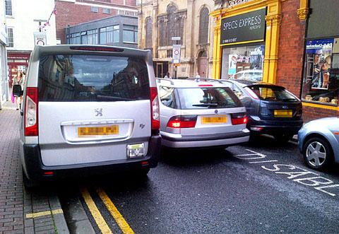 TIGHT FIT: A car squeezing its way past a taxi sitting partly on the pavement on double yellow lines in Trinity Street