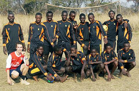 UNITED BY FOOTBALL: Joe Lovell in his Arsenal kit with some of the youngsters in north-western Zambia in their strips.