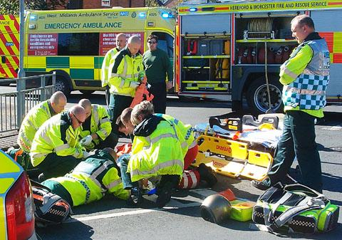 EMERGENCY: Paramedics treat the crash victim by the road (reader's picture)