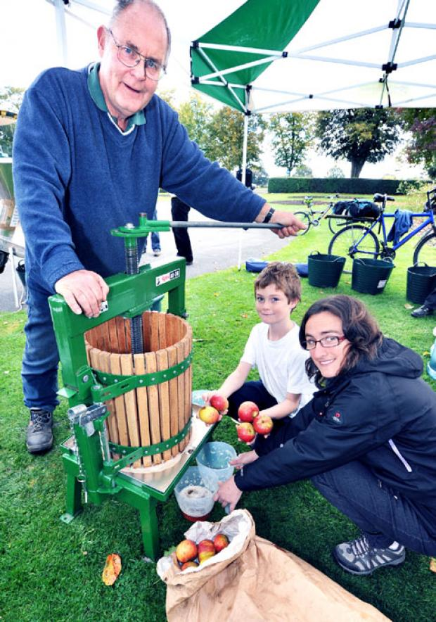 SQUUEZE: Volunteer Arthur Rowe operates the apple press while Ben Sparrow, nine, and Dawn Lewis collect the juice (41153201)