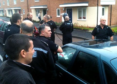 GOING IN: Police officers get ready to go into a block of flats in Warndon