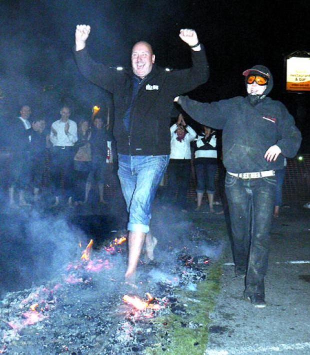 SMOKING: Pete Grinnall celebrates as he safely makes it across the bed of hot coals.