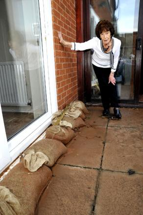 WATER-DAMAGED: Joan Green with sandbags outside her Dines Green home. Picture by Nick Toogood. 5112209104