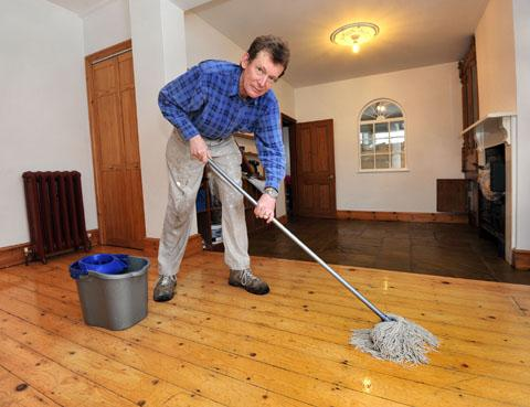 mopping up: Iain Smith cleans the remaining floodwater from his home – but is expecting the water to come in againn. Picture: John Anyon. 0113212501