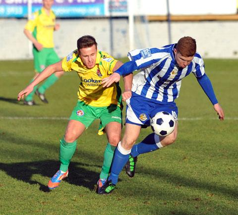HOLDING ON: Worcester City two-goal hero Danny Glover looks to breakaway from his marker but the Vauxhall Motors' player has a grip of his shorts.
