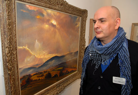 STRIKING: Nigel Marshall, gallery assistant, beside a Dame Laura Knight painting entitled Autumn Sunset. 0513235302