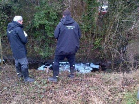 Environment Agency staff tackle oil at a stream in Malvern