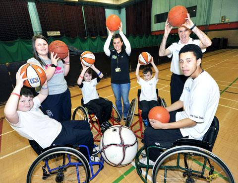 SHOOT SOME HOOPS: Trying their hands at wheelchair basketball are, from left, James Milner, aged nine, Lewis Gainers, 10, Gethyn Fox, eight, and Kieran Potter, 15, with coaches Alice Keylock, Hannah Cox and Paul Stirling. 0813250601