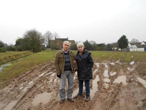 SODDEN: Nigel and Janice Jarvis on the muddy land they have to cross to reach their mobile home near Kempsey Common.