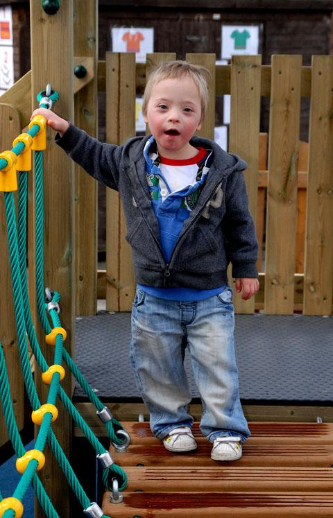 HOLD ON TIGHT: Ethan Harding, aged three, walks on the rope bridge.