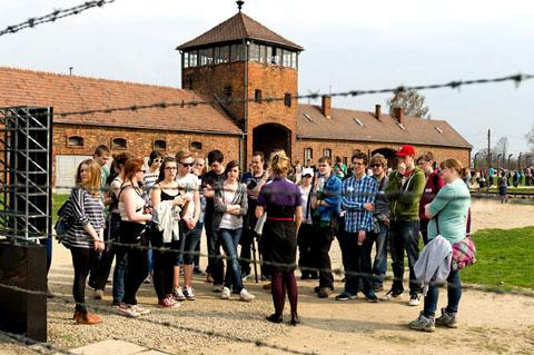 SCENE OF EVIL: Worcestershire students and teachers gather at the infamous gates to the Auschwitz-Birkenau concentration camp.