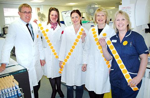 A BRIGHT IDEA: John Howles, Carla Newland-Baker, Angie Williamson and Louise Hepburn, from the Blood Sciences laboratory, with Gill Godding, lead transfusion practitioner. Inset: The stickers read 'Priority sample patient discharge'.
