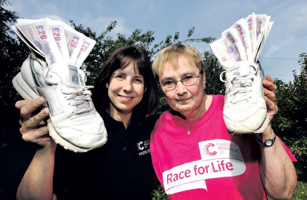 pay in sponsorship: Janet Burley, right, from West Malvern raised £1,050 for Cancer Research at Race for Life on June 16. She hands over her donation to Paula Young, Cancer Research press officer. Picture John Anyon. 3513391701