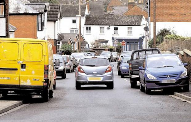 ACTION NEEDED: A car makes its way down Fort Royal Hill with other vehicles parked on both sides of the pavement.