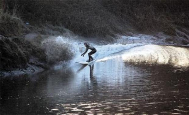 RIDING THE BORE: A surfer on an earlier bore