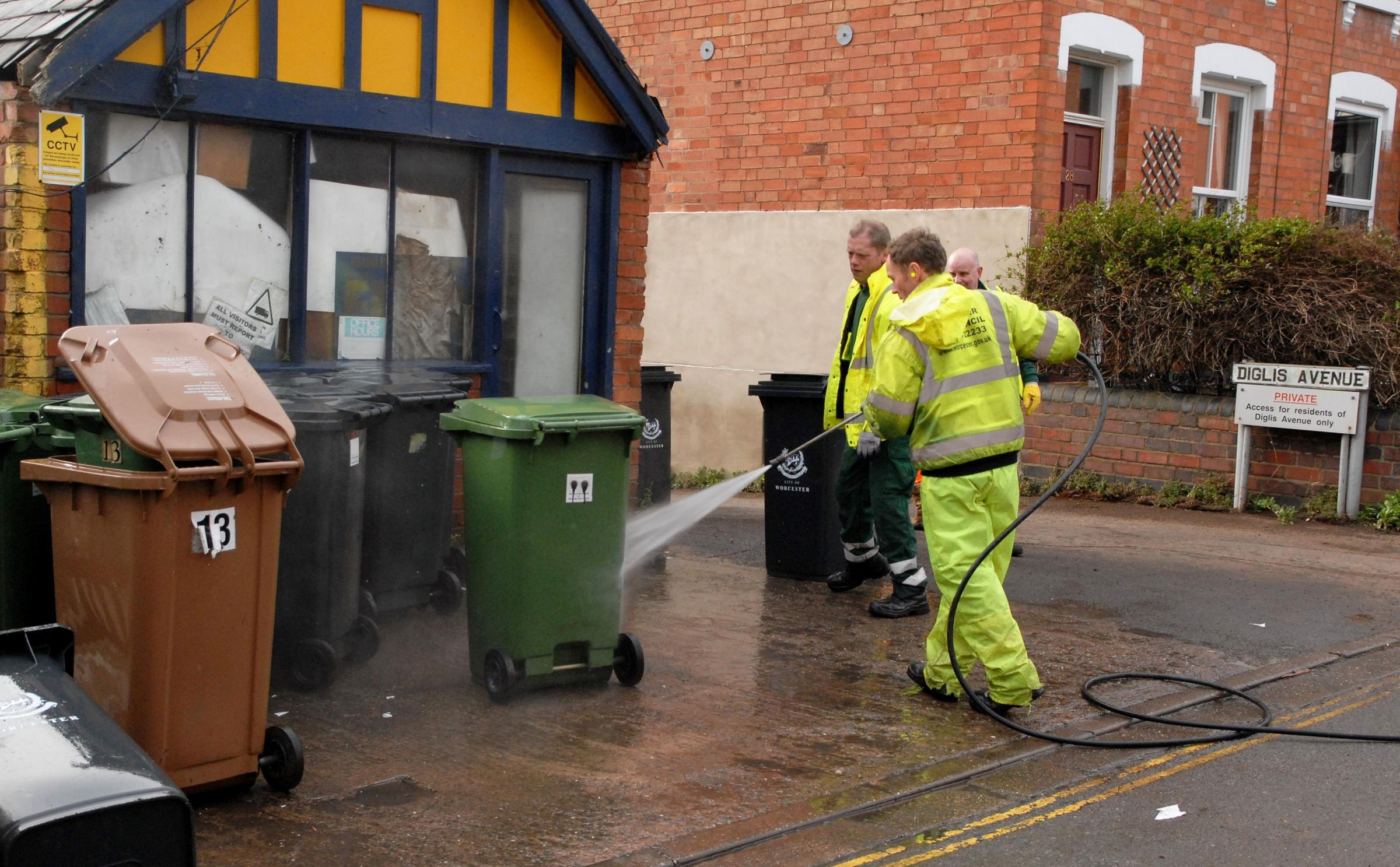 THE BIG CLEAN-UP BEGINS: Worcester City Council workers hose down wheelie bins which were floating in flood water last week.