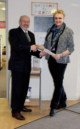 Councillor Tony Miller hands over his donation to Acorn's Children's Hospice