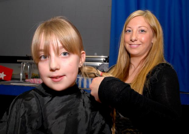 Worcester News: 1014538801 Paul Jackson 07.03.14 Worcester St Clements Primary School pupil Caitlin Jones, nine, has her hair cut off to raise money for Kyeleni Primary School in Kenya by Natalie Peel from Blow Your Top. Her hair is being donated to Princess Cancer Trust