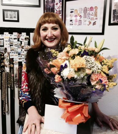 Owner of Second Hand Rose Clare Bridge with the flowers given to the store in a random act of kindness.