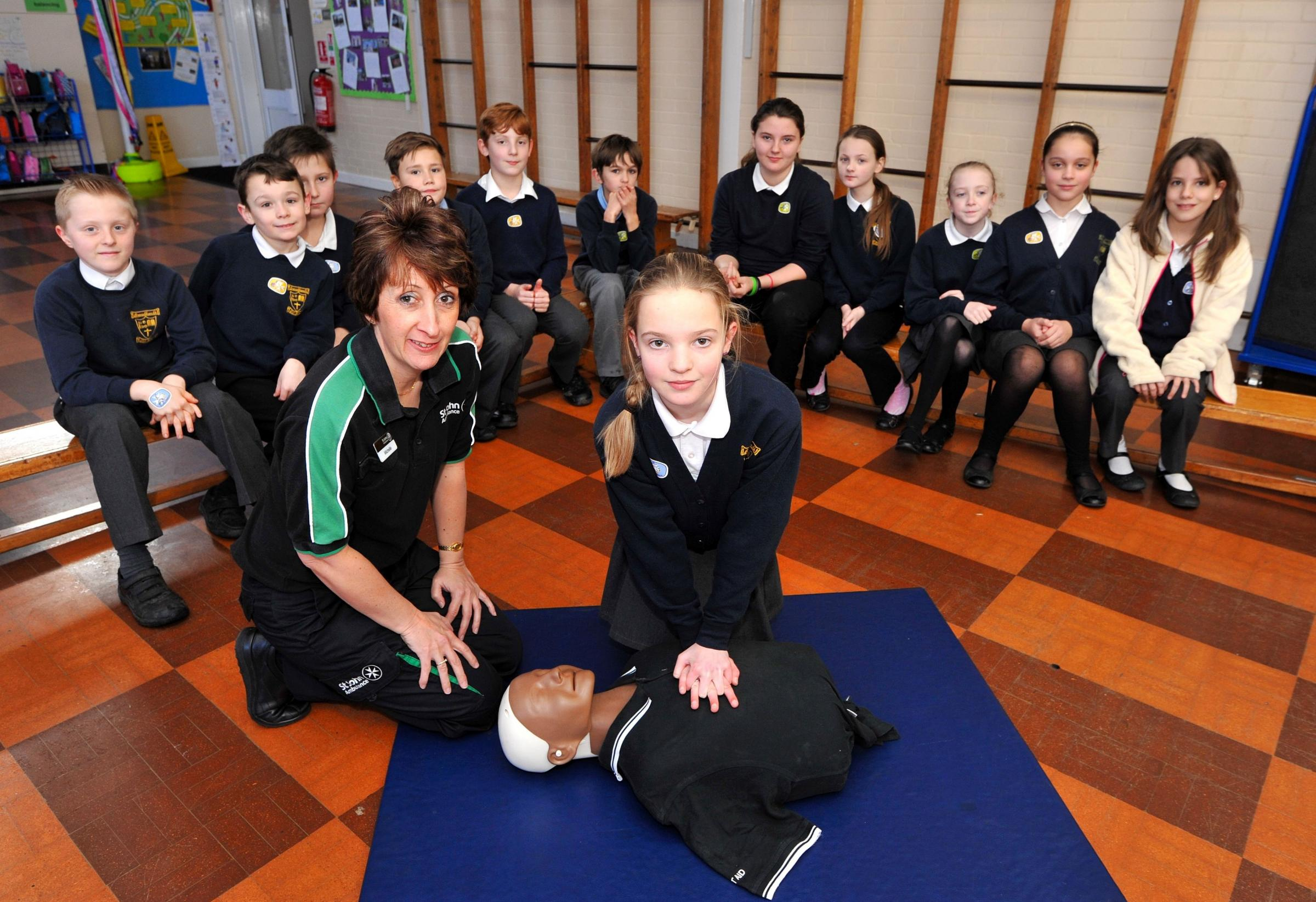 St John's Ambulance School's trainer Michelle James shows Lily Smith, 10, and her fellow Year 6 classmates resuscitation using a dummy when she visited Broadheath Primary School. Picture by John Anyon. 0614520801
