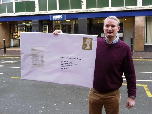 Louis Stephen handing in the petition via the RBS bank in St Nicholas Street, Worcester.