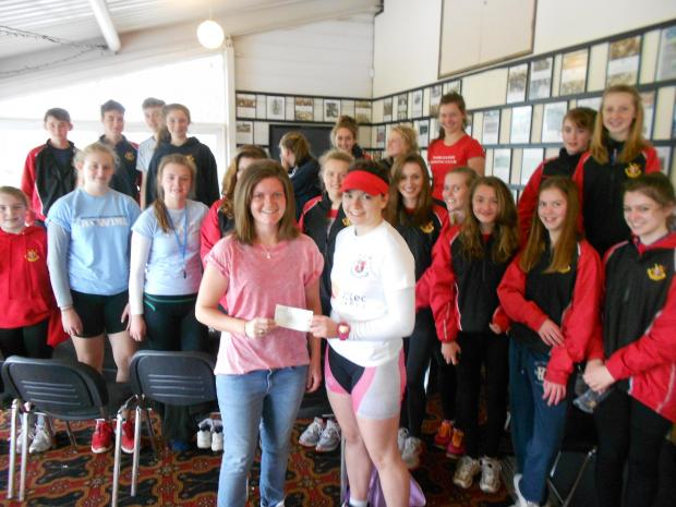 Juniors Squad captain Izzy Friedlander presenting Hannah Lawton with the cheque