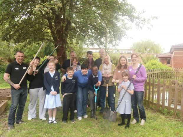 Volunteers from Perry Wood Manor residential care home help with gardening at Perry Wood Primary and Nursery School
