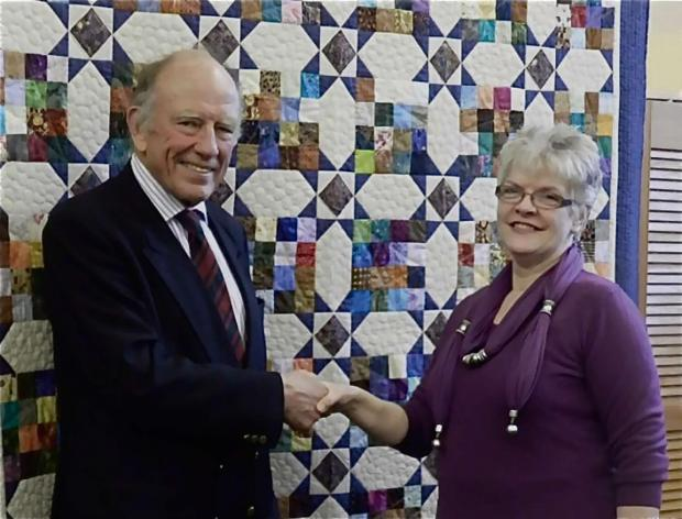 Worcester News: Retired lieutenant colonel Gerry Taggart of Powick, leader of Team Sapper, with Yvonne  Jenkins of Malvern Quilters and the quilt they both hope will help wounded soldiers battle back to better health.