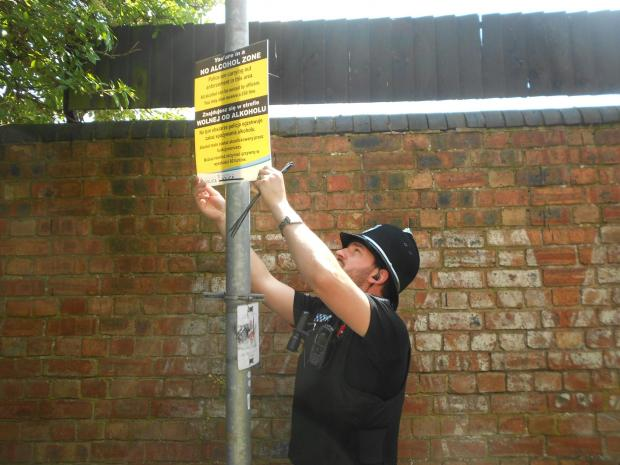 PC Alex Denny puts up one of the signs in the alley at the end of Sansome Place