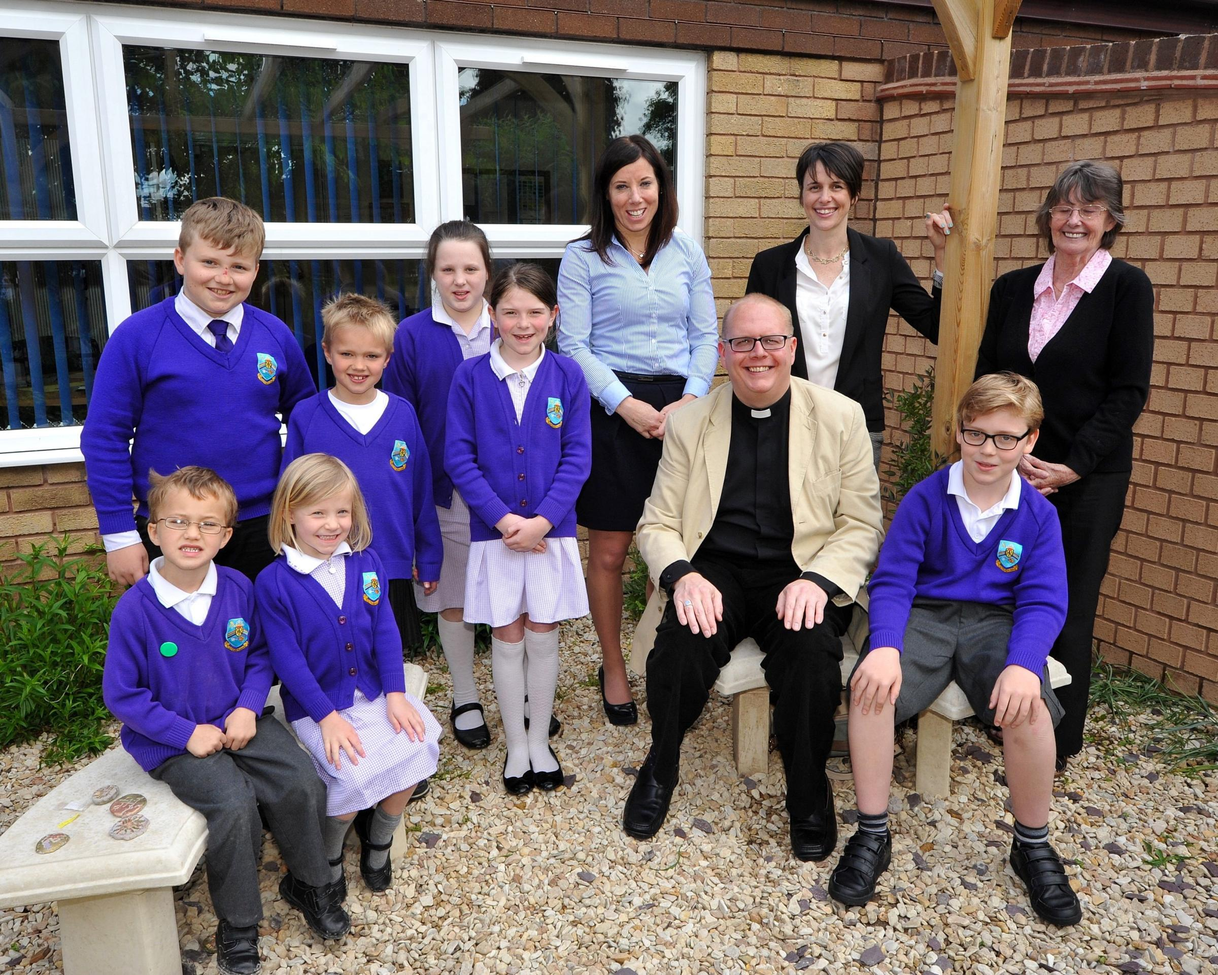 Our Lady Queen of Peace RC Primary School in St Johns has received a good report for it's religious provision.Head Teacher, Gwen Fennell, RE Co-ordinator, Katie Howarth, Governor, Vivienne Cause, Chairman of Governors, Father Paul Whieldon with pupils