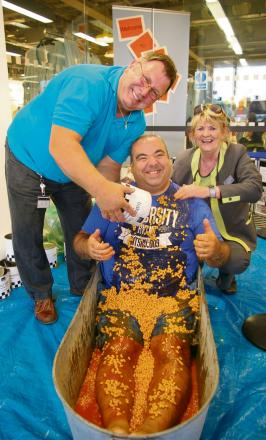 Marks and Spencer manager Andy Oliver undergoes the bean ordeal, assisted by staff members Brian Bennett and Helen McKeown. Picture by Stan Hubbard.