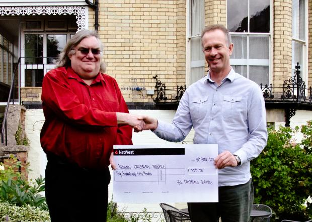 Worcester News: Ian Parker, manager of Malvern's G4S Children's Services in Malvern, presents a cheque for £150 to Andy Mapp, towards the Midsummer Mappfest's support of Acorns Children's Hospice.