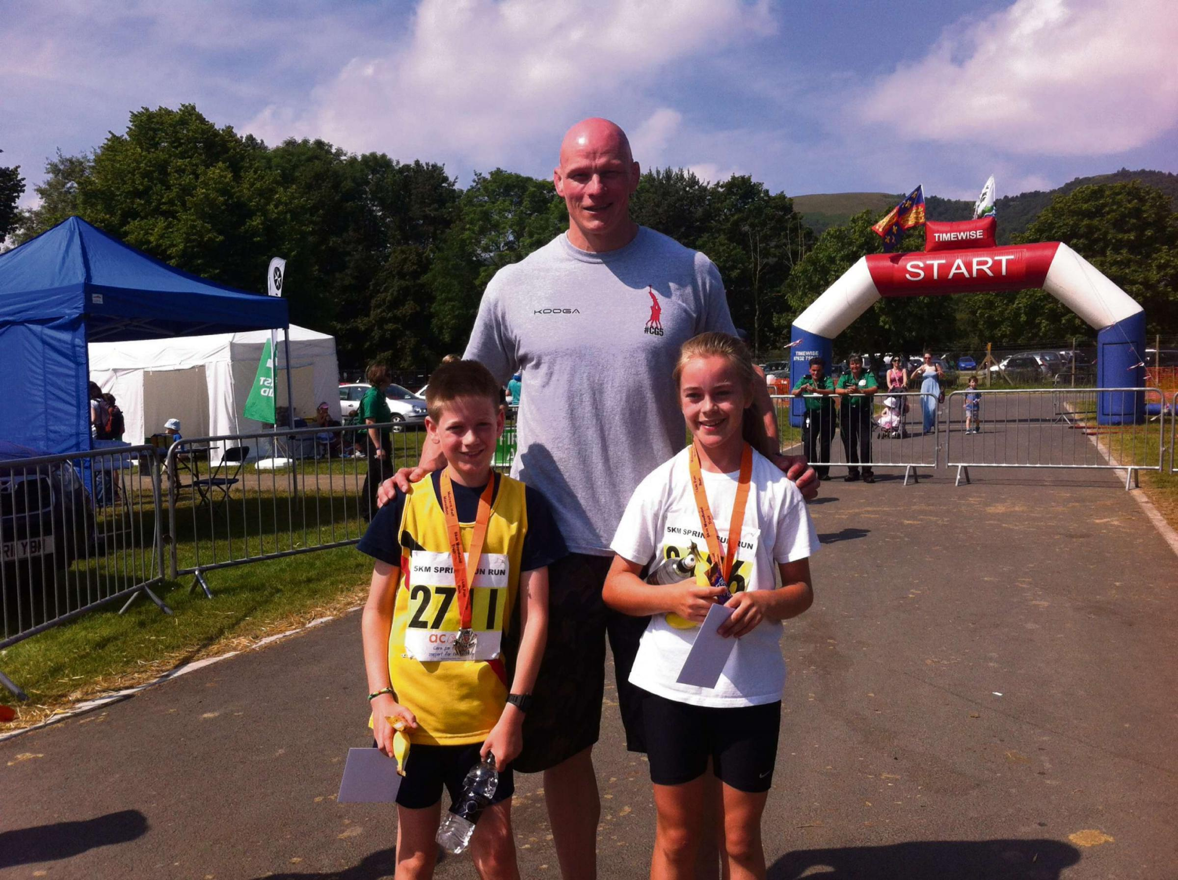RUNNERS: Riley Carpenter and Libby Dickenson are presented their medals by former Worcester Warriors player Craig Gillies, who was on hand to start a ra