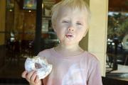 Young Child Making Funny Face while Eating a Doughnut (15879299)