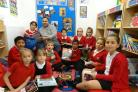 Dad Mumtaz Waliat reads with Stanley Road Primary School in the school's library.Gutiera Grigaityte, Lily Marshall, Jery Permana, Harry Knight, Charlotte Wills, Yai Ceesay, Iris Collett, Lizzie Miller, Akeel Hussain, Shayan Ali and Qurratulain Tabassum
