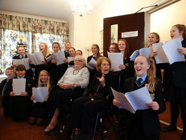 BISHOP PEROWNE: Students Jill Morphey and Bessie McConkey sing with residents from The Shrubbery Care