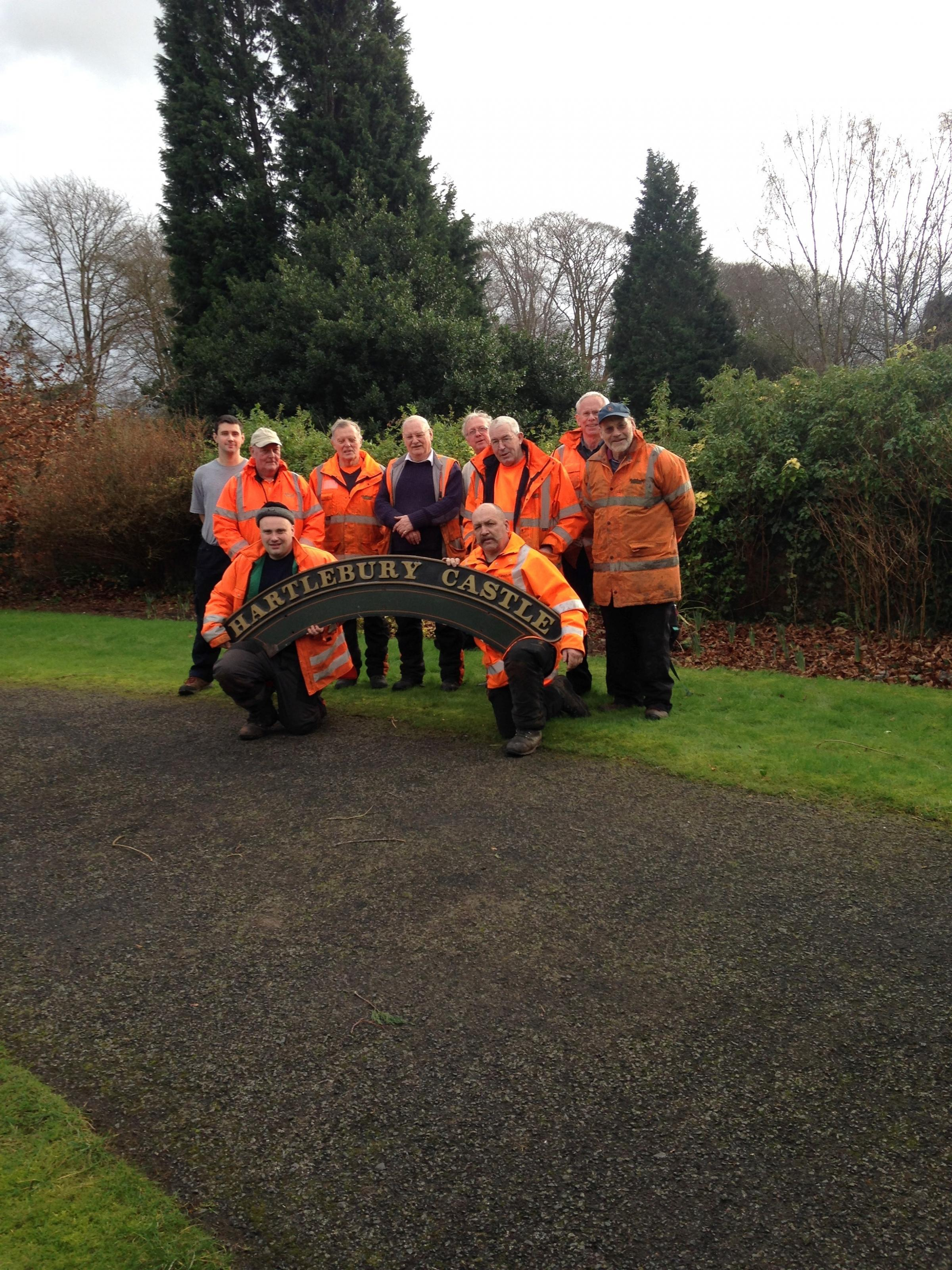Severn Valley Railway volunteers pose with the Hartlebury Castle locomotive's name plate after spending the day clearing the grounds of the historic building