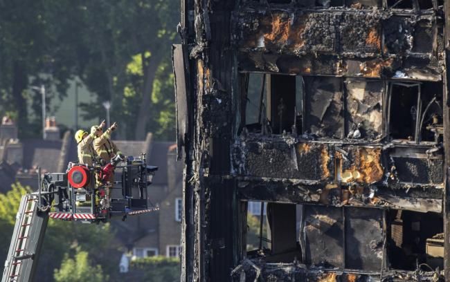 Fire service personnel survey the damage to Grenfell Tower in west London after a fire engulfed the 24-storey building on Wednesday morning. PA